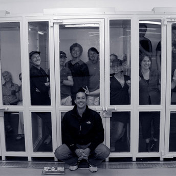 David Vadiveloo posing with the cast and crew in the holding cells at the police station.