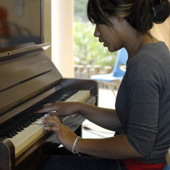 An attendee of the Community Prophets workshop playing a piano.